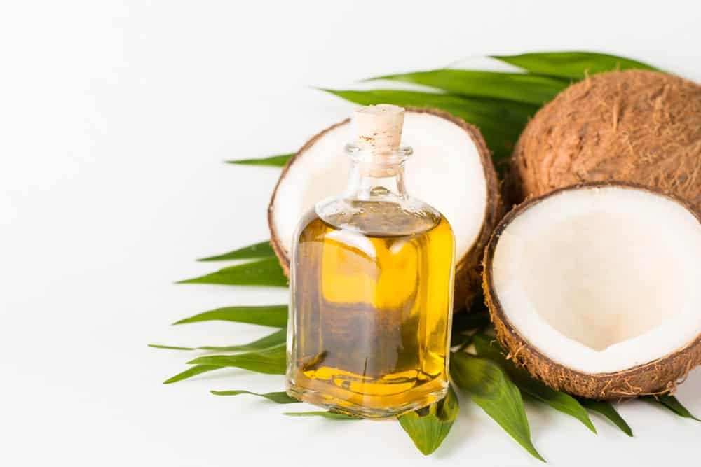 A glass bottle of organic coconut oil with raw coconuts on leaves.