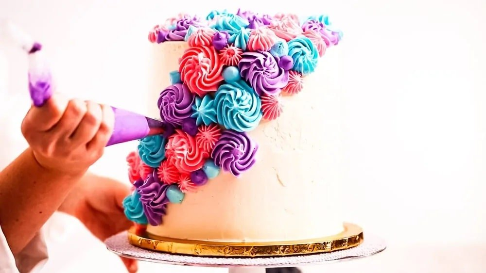 Adding colorful frosting to a layered cake.