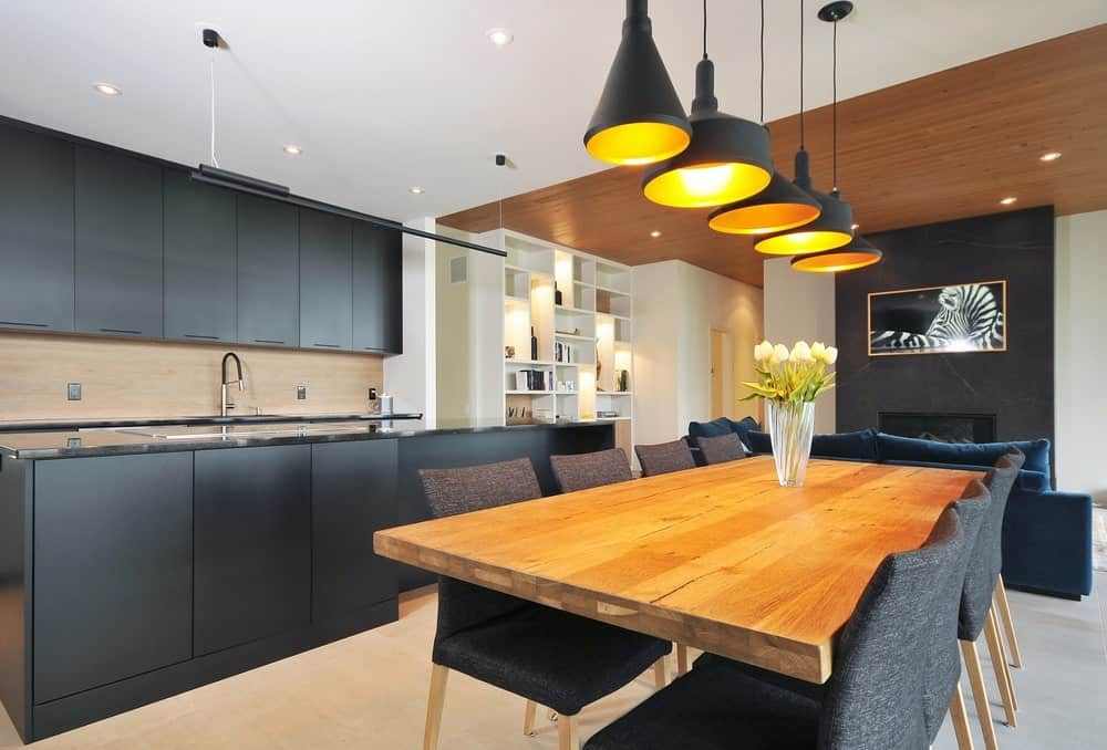 This elegant dining area uses the black kitchen as a nice background to contrast the white ceiling. This also matches the black pendant lights and the black cushioned chairs surrounding the wooden dining table.