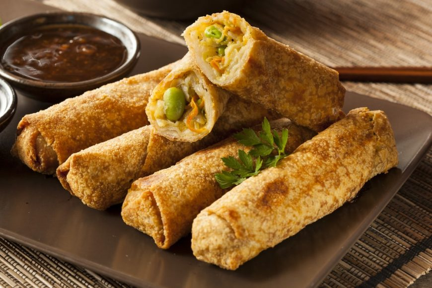 A plate of homemade vegan egg rolls with a dipping sauce on the side.