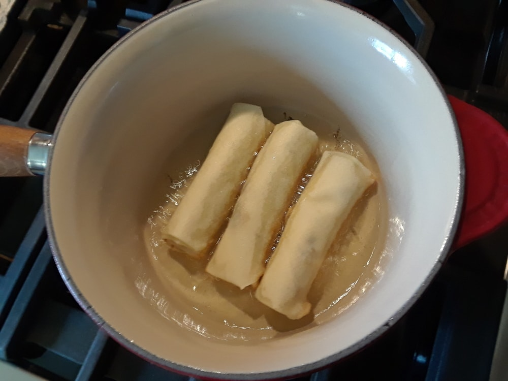 The rolls placed in a pot with oil.
