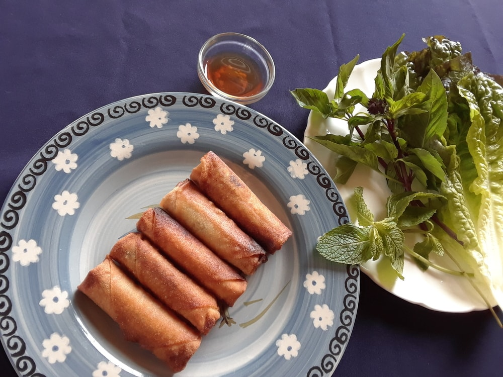 The finished vegan egg rolls placed on a plate with dipping sauce on the side.