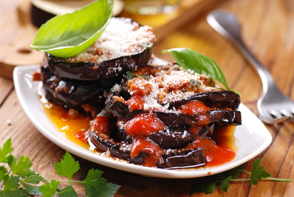 A lovely plate of vegan eggplant parmesan with basil.