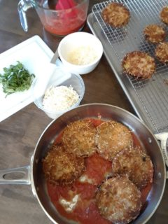 The fried eggplant slices are placed in a pot with the tomato puree.
