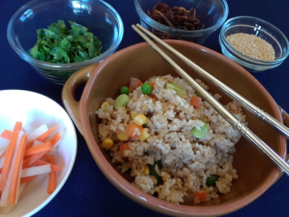 A lovely bowl of vegan fried rice with optional toppings on the sides.