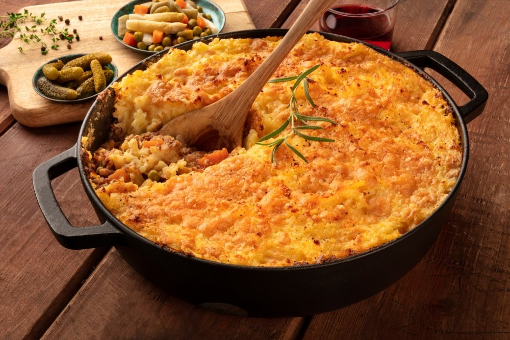 Homemade Shepherd's pie in an iron skillet on a wooden surface.