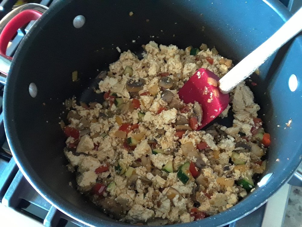 The tofu is mixed into the cooked ingredients.