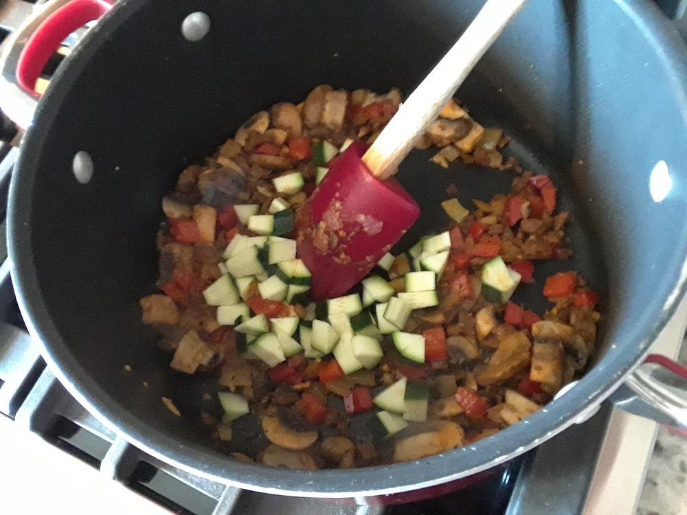 The zucchini is added into the ingredients cooking in the pot.