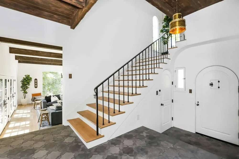 This is a simple yet charming foyer with a black stone brick flooring to pair with the black railing of the staircase. These contrast with the pure white walls and doors.