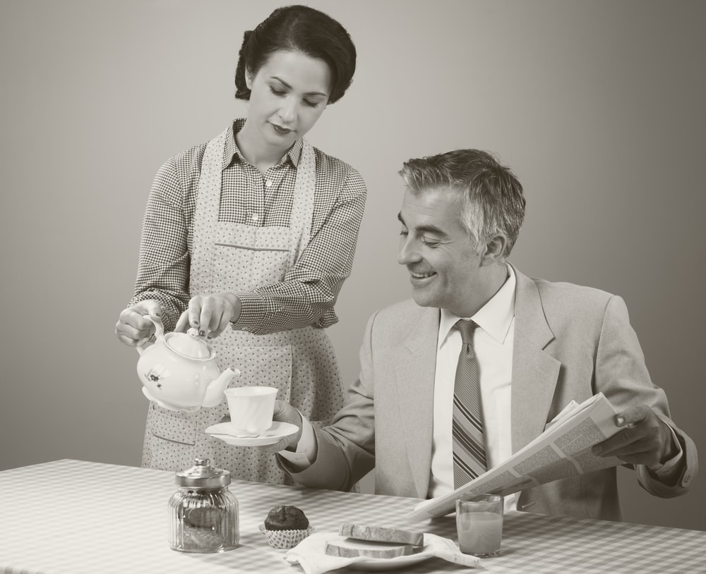 1950s image of a wife wearing apron and pouring tea for her husband while he sits at the table for breakfast with newspaper in hand.