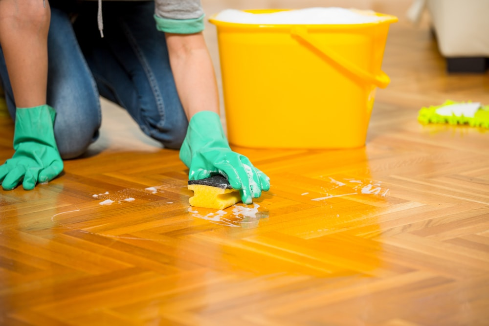 Person down on the knees cleaning the floor with rubber gloves, sponge, and a bucket of soap solution.
