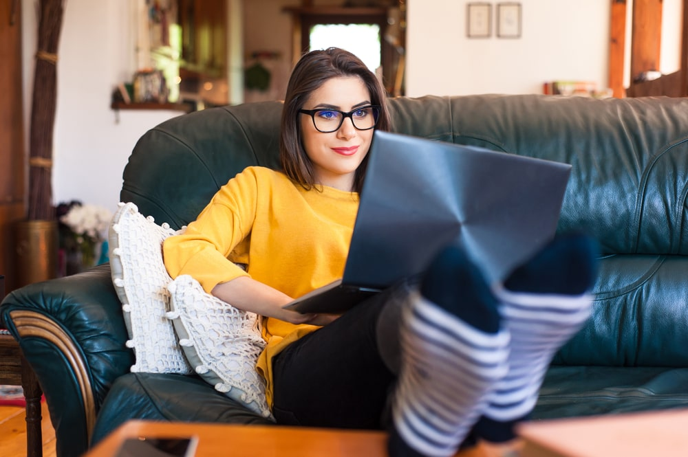 Woman sitting on a couch with her feet propped on the coffee table and working on her laptop.