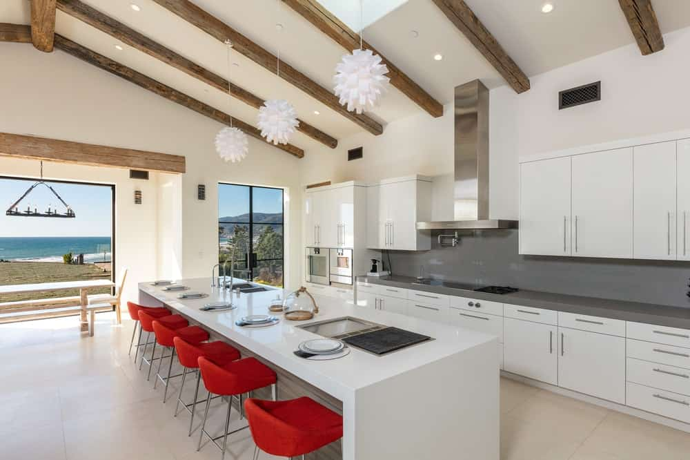 This bright and white kitchen has a long white waterfall kitchen island paired with contrasting red stools. Across this is the cooking area with a dark gray backsplash.