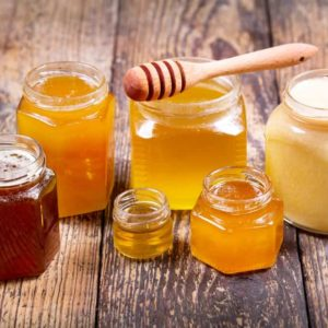 Jars of different honey on a wooden surface.