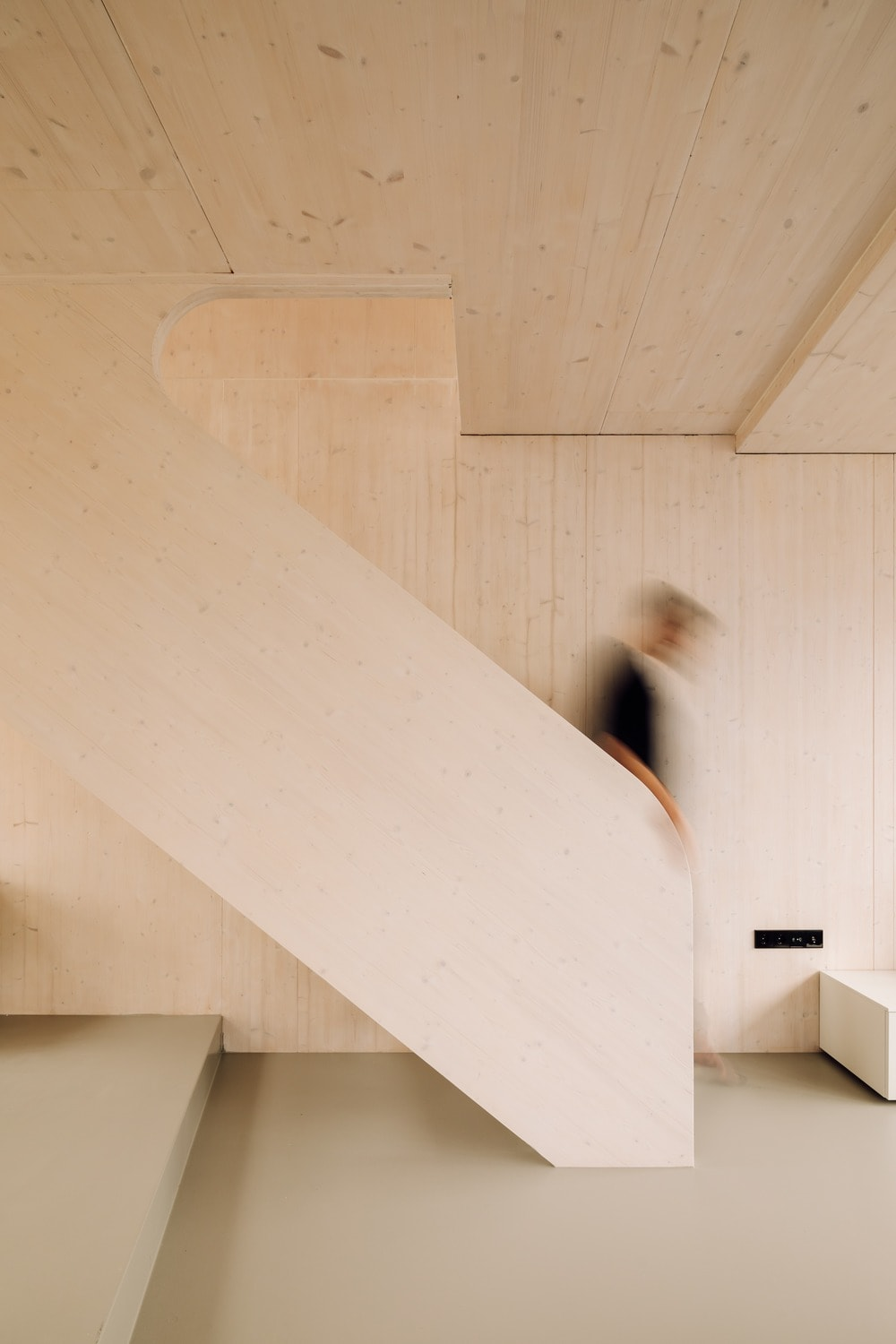 This is a close look at the staircase that has a low woodenborder that makes it blend with the walls and ceiling.