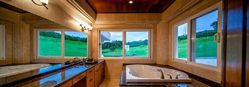 The primary bathroom has a drop-in tub with sweeping views of the lush outdoors. Image courtesy of Toptenrealestatedeals.com.
