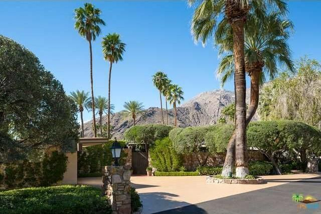 The gate to Kirk Douglas's former home in Palm Springs, CA is surrounded by palm trees. Image courtesy of Toptenrealestatedeals.com.