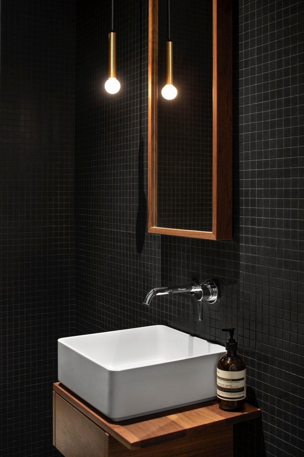 This is a close look at the modern white freestanding sink of the bathroom on a wooden floating vanity. This stands out against the black tiles of the wall with a wall-mounted mirror with wooden frames.