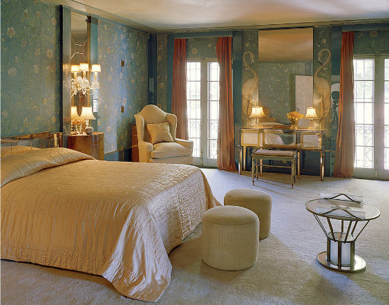The primary bedroom has interior wallpaper, carpeting, and seating areas. Image courtesy of Toptenrealestatedeals.com.