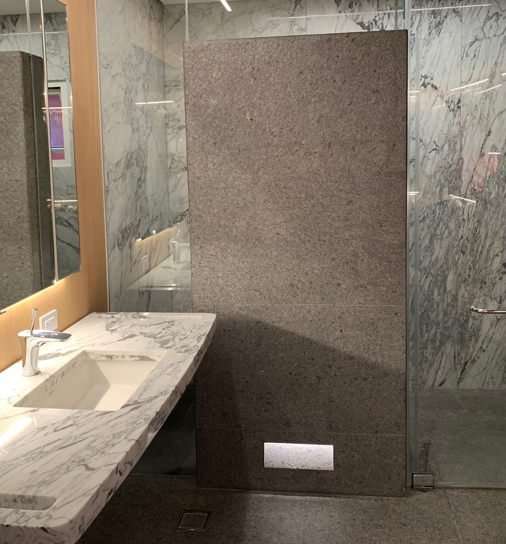 This is the bathroom with a floating white marble sink next to the glass-enclosed walk-in shower area.