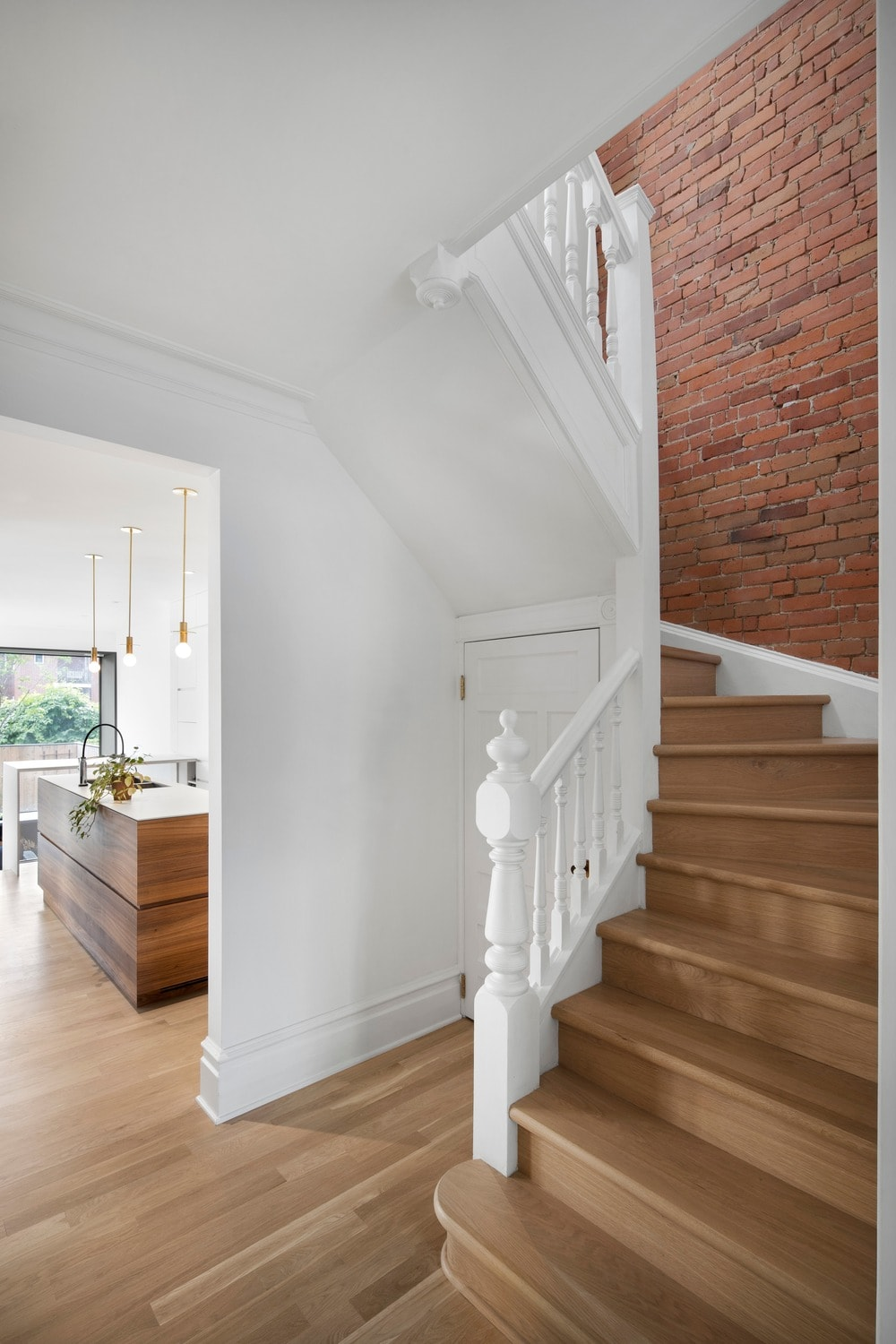 A few steps from the kitchen is this staircase that has wooden steps to match the hardwood flooring. These are then contrasted by the white wooden railings and the red brick wall.