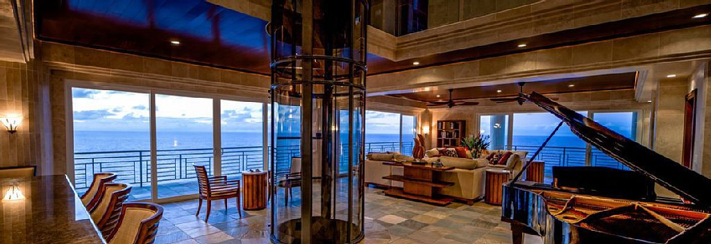 An open concept living interior and the residential elevator in the middle. Image courtesy of Toptenrealestatedeals.com.