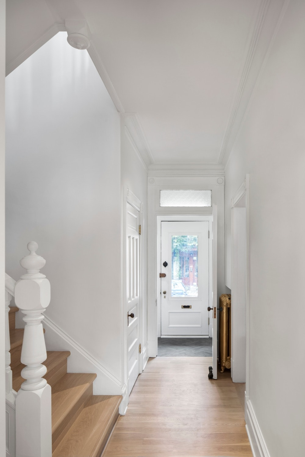 This is a look at the hallway and the white wooden back door at the far end. This door has a glass panel and a transom window that brings in natural lights to brighten the white walls and ceiling.