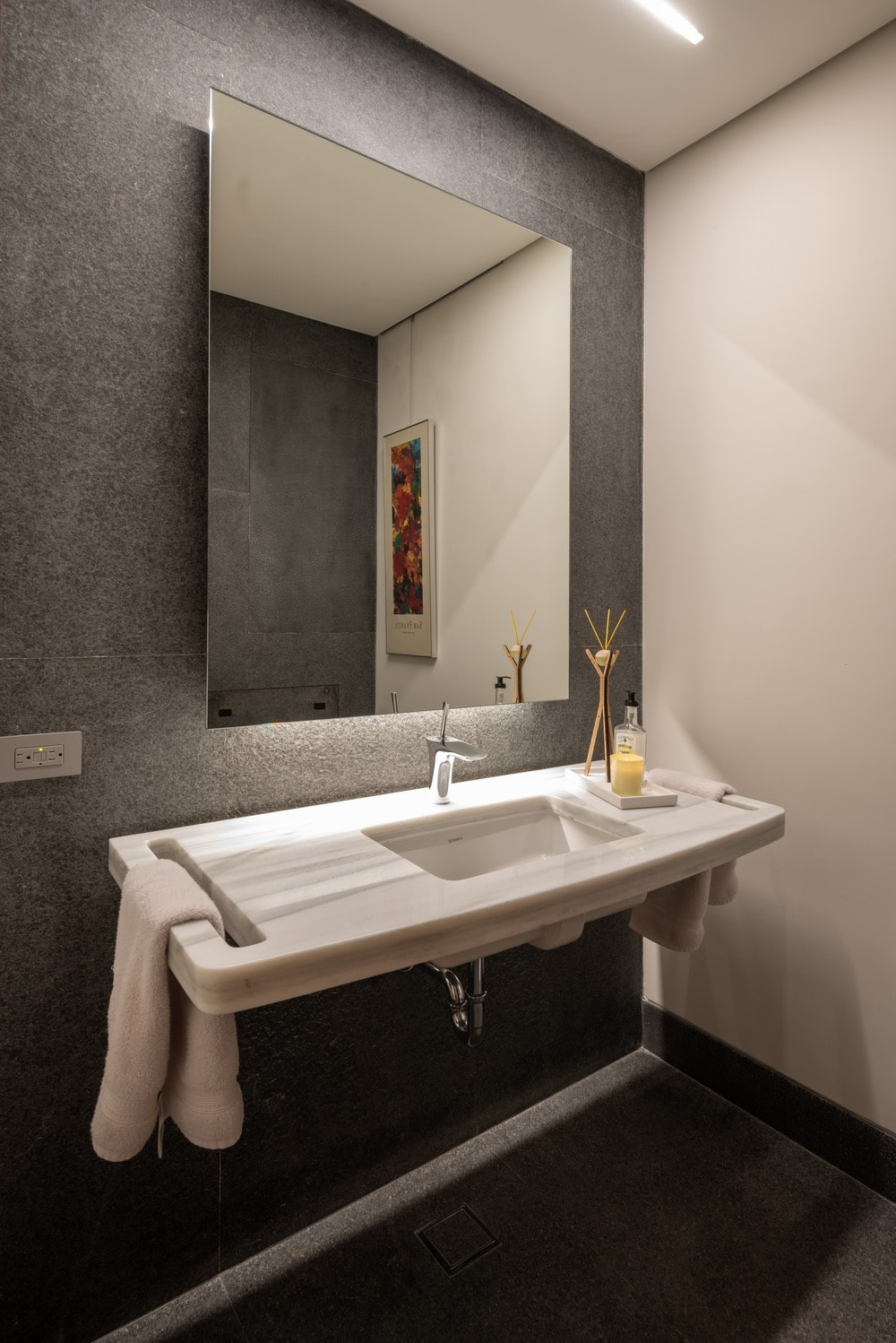 This other bathroom also has a floating white marble sink with a built-in towel rack and topped with a large wall-mounted frame-less mirror.