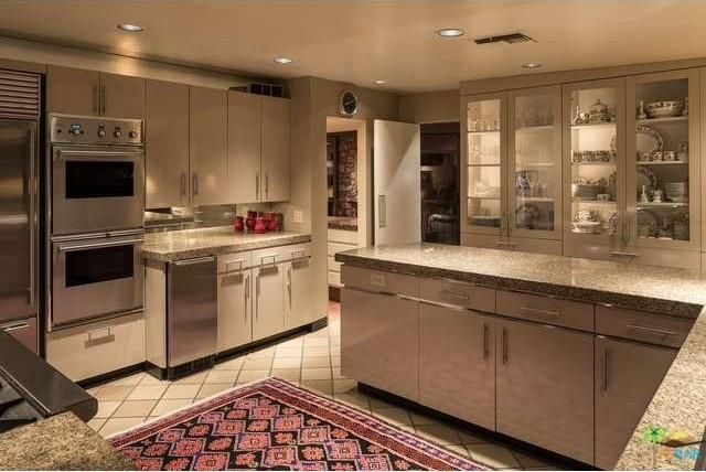 The kitchen has glossy cabinetry and stainless steel appliances. Image courtesy of Toptenrealestatedeals.com.
