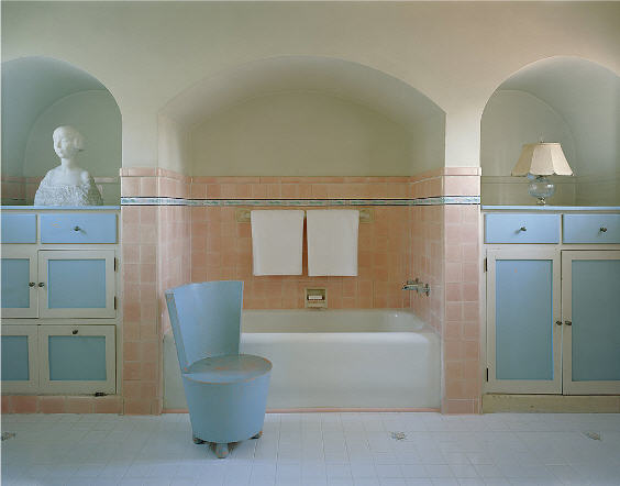 The primary bath has pastel-colored cabinetry, chair, and tile walls, and an alcove tub. Image courtesy of Toptenrealestatedeals.com.