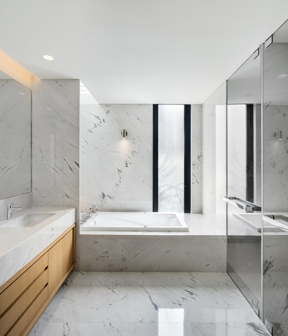 This other bathroom has bright white marble to its floor, walls and the bathtub housing at the far end by a narrow window. Next to it is the glass-enclosed shower area across from the floating vanity.