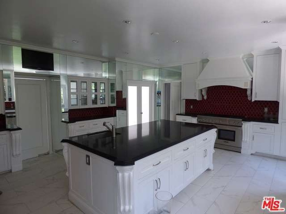 A massive kitchen island with black countertop in the spacious white kitchen. Image courtesy of Toptenrealestatedeals.com.