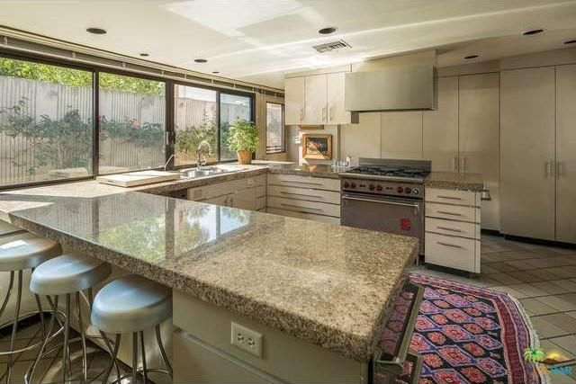 A U-shaped kitchen with a peninsula bar and large windows. Image courtesy of Toptenrealestatedeals.com.
