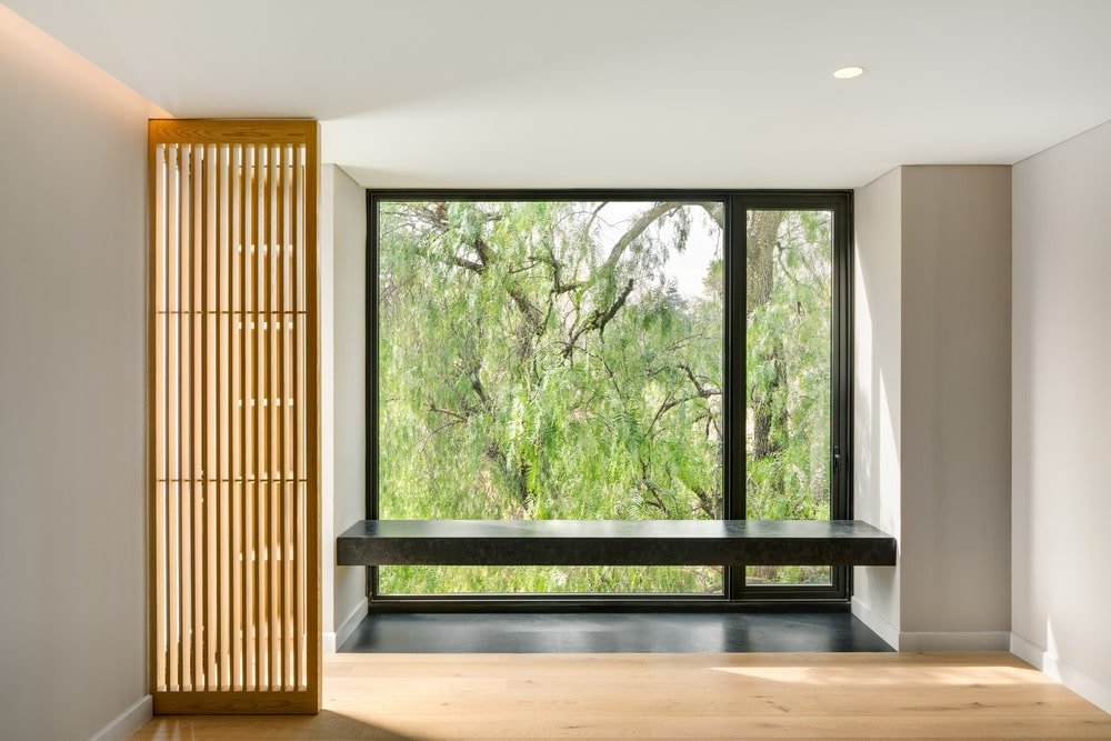 This is a look at the bedroom that has a built-in bench on the far side by the large glass wall with a view of the landscape outside.