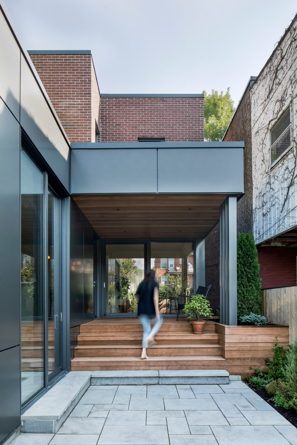 This is another look at the main entrance of the house featuring the wooden deck steps that stand out against the surrounding metal and glass elements of the house exterior.