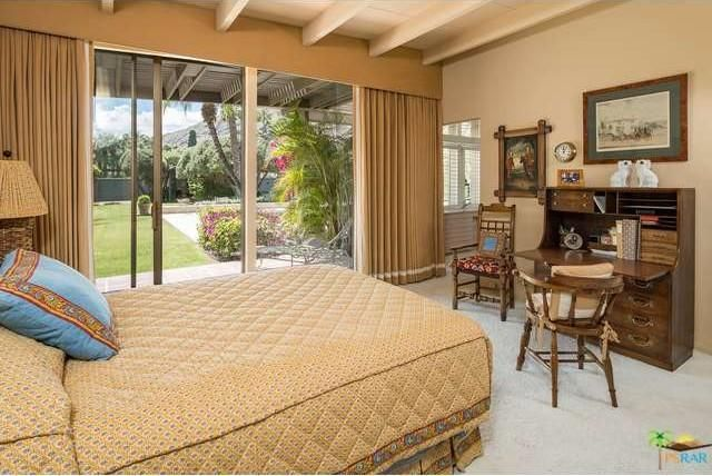 The primary bedroom has a small seating area facing the bed. Image courtesy of Toptenrealestatedeals.com.