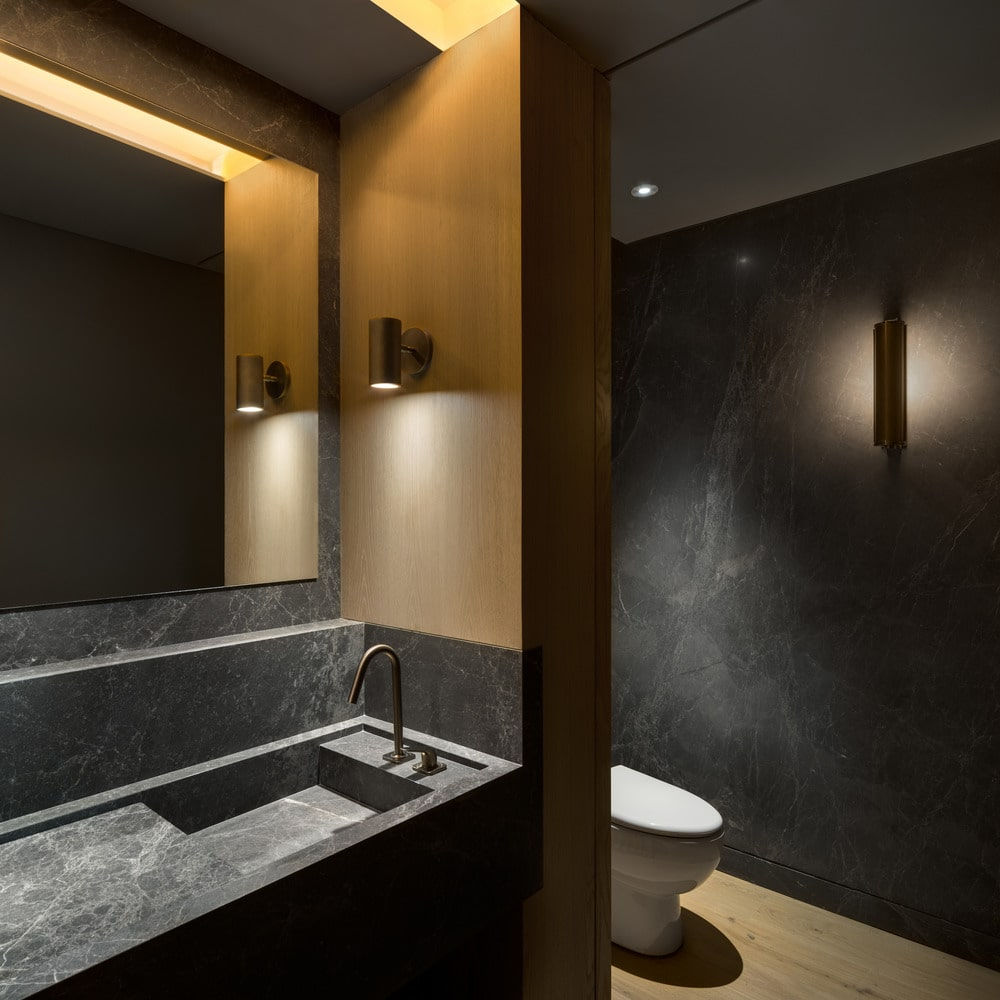 This is one of the bathrooms that has a dark gray marble tone to the walls and its vanity countertop adorned with a mirror and sconces.