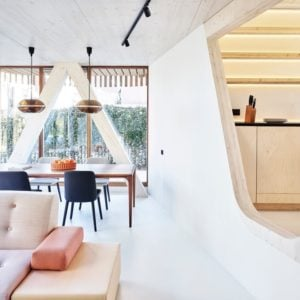 Behind the beige sofa of the living room area is a dining area that has a wooden dining table topped with pendant lights.
