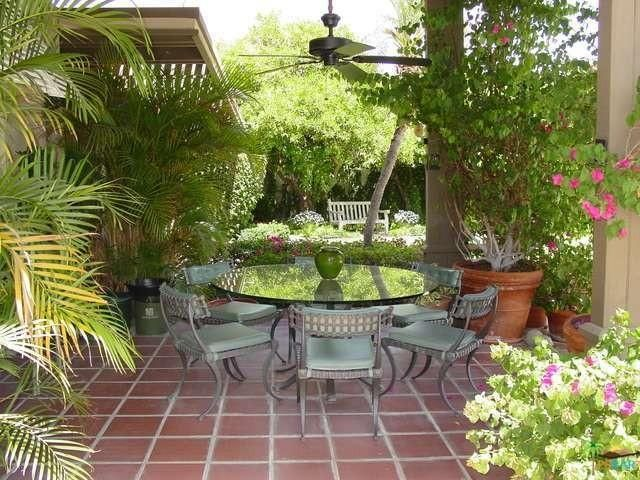The garden patio with a round glass table and six chairs under a ceiling fan is surrounded by green potted plants and flowers. Image courtesy of Toptenrealestatedeals.com.
