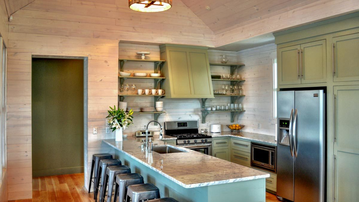 Kitchen with green cabinetry, stainless steel appliances, and a granite top peninsula fitted with an undermount sink.