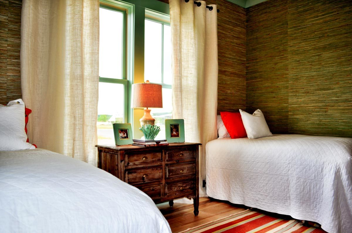 This bedroom offers two beds, a center nightstand, and a large green framed window dressed in sheer draperies.
