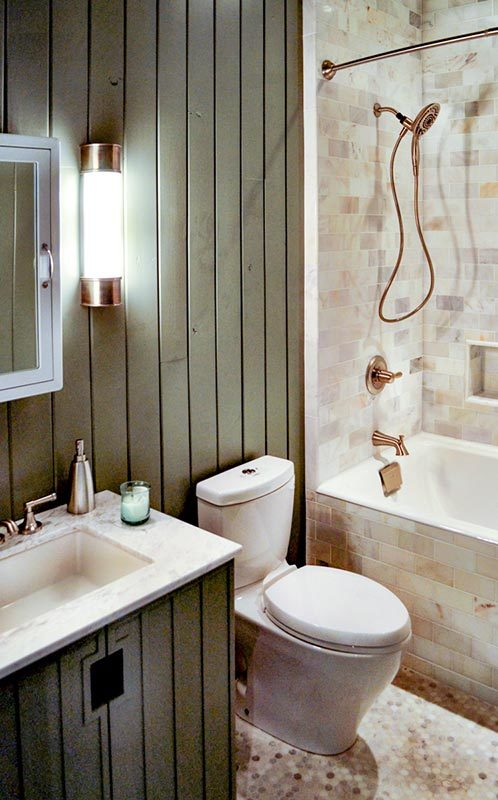 The bathroom is equipped with a sink vanity, a toilet, and a tub and shower combo accented with copper fixtures.