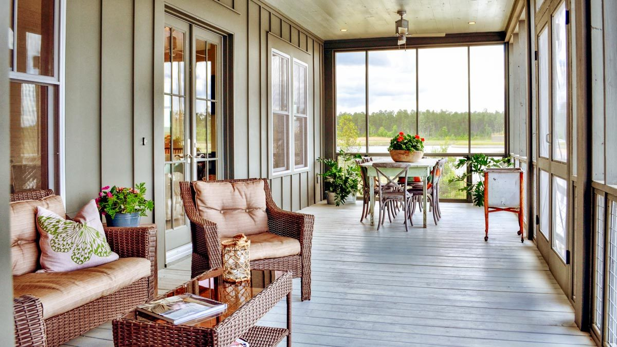 Wooden dining set, wicker armchairs, and a matching coffee table fill the screened porch.