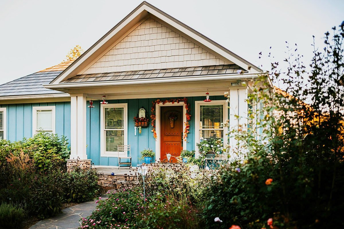 Home entry with a wooden front door and a covered porch lined with decorative pillars.