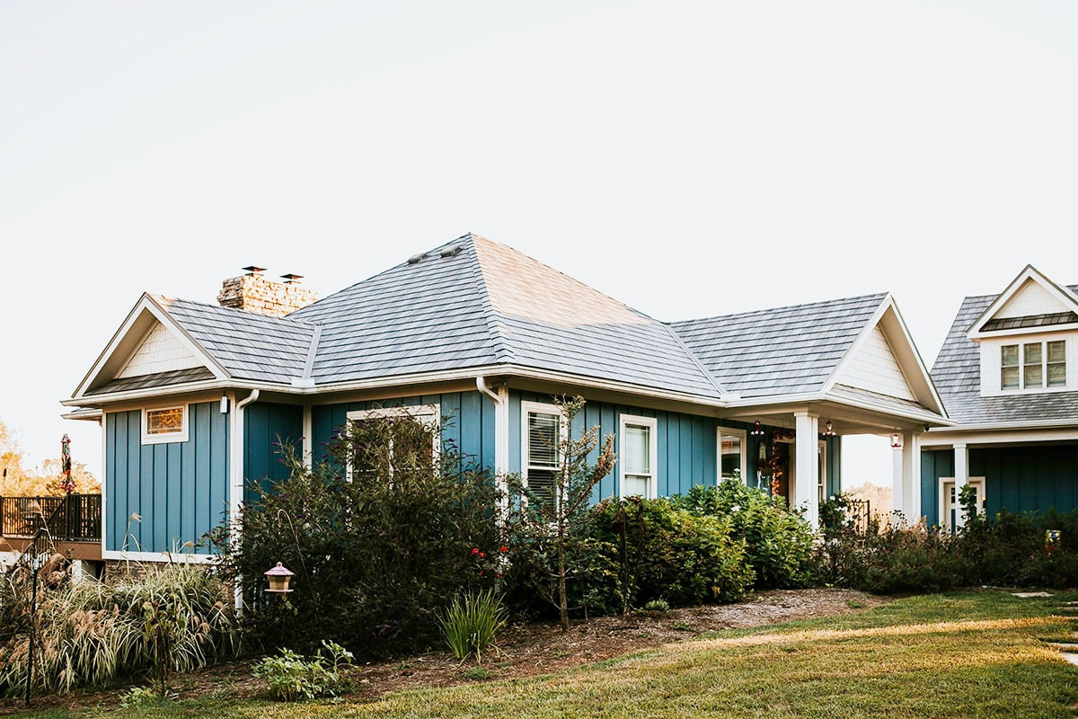 Angled front view showing the blue vertical exterior siding along with hipped and gable rooflines.