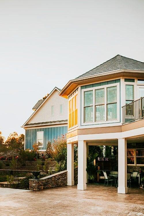 A gazebo-like covered deck under the striking turret surrounded with glazed windows.