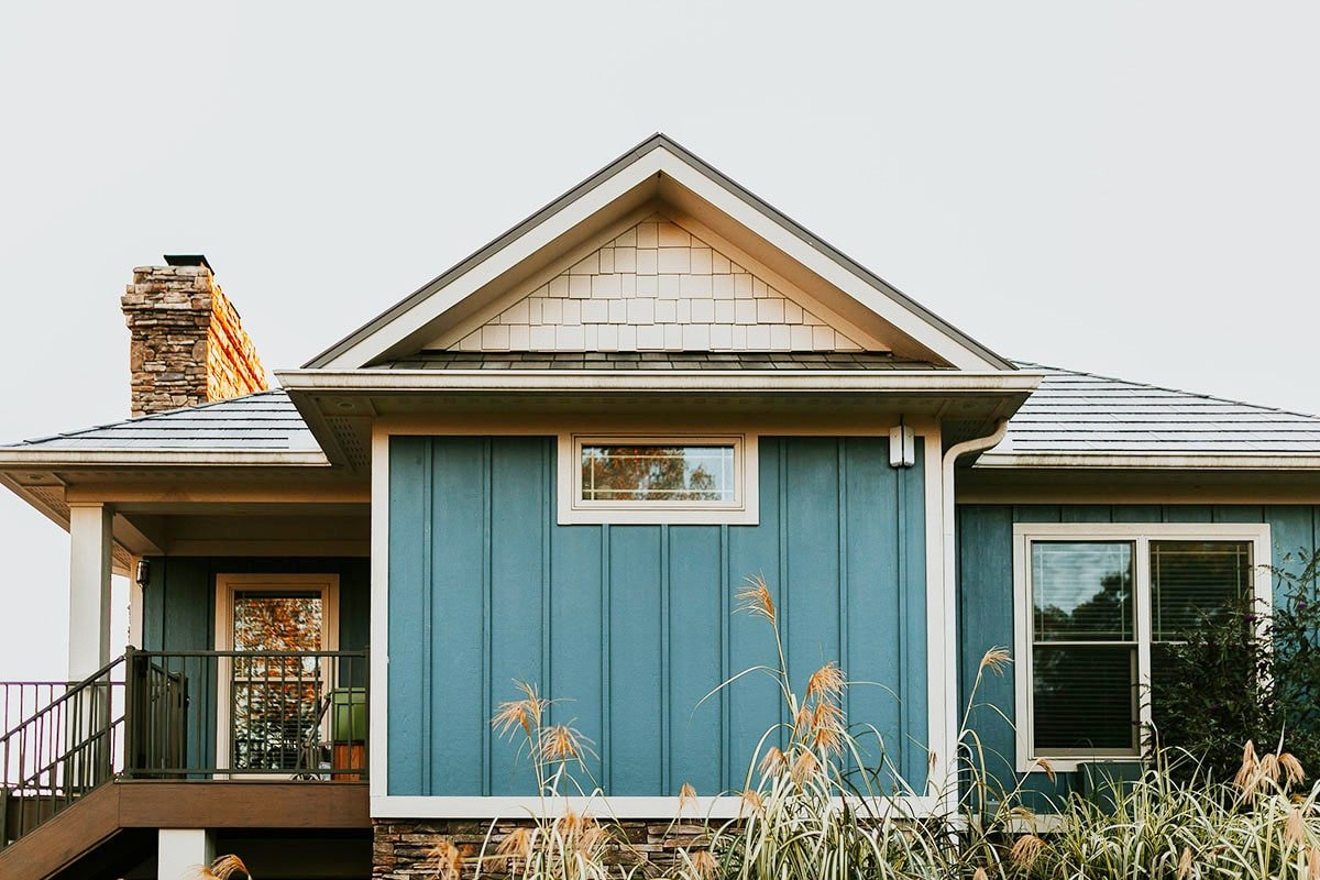 Hipped and center gable roofs top the bungalow house with vertical exterior siding and covered deck.