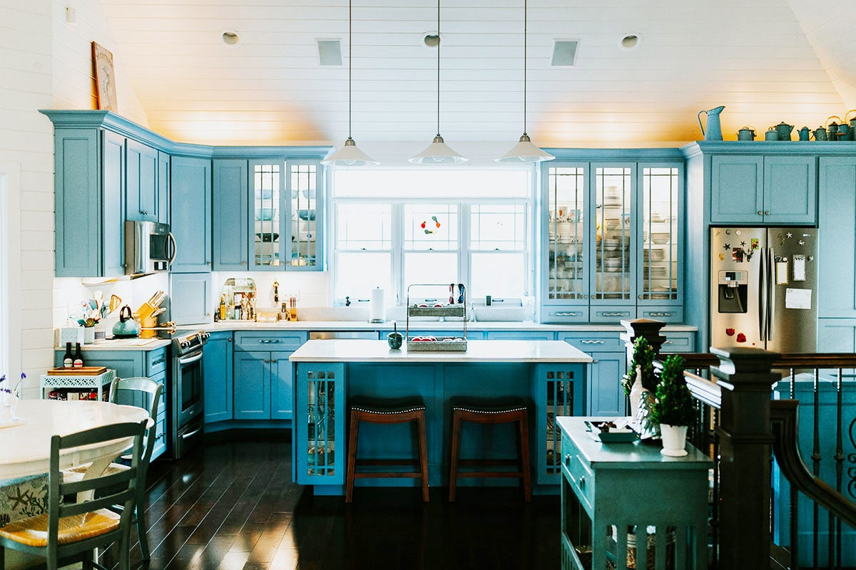 The kitchen offers blue cabinetry, stainless steel appliances, and a quartz top island paired with wooden stools.