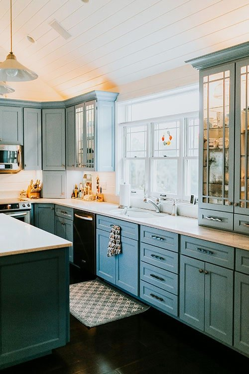 Natural light from the three-panel windows above the sink brightens the kitchen.