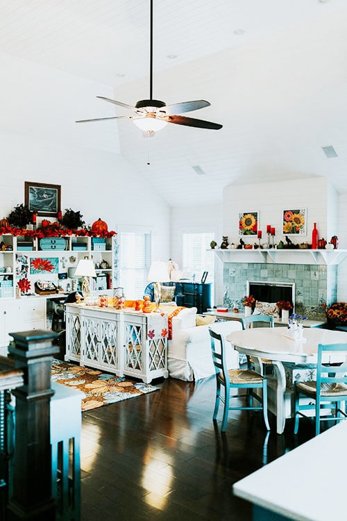 Shared dining and living room with a ceiling fan, round dining set, white built-ins, and a stylish mirrored cabinet sitting behind the sofa.